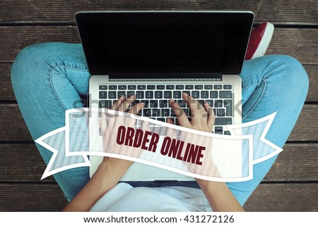 Young women holding laptop writen Order Online on it - stock photo