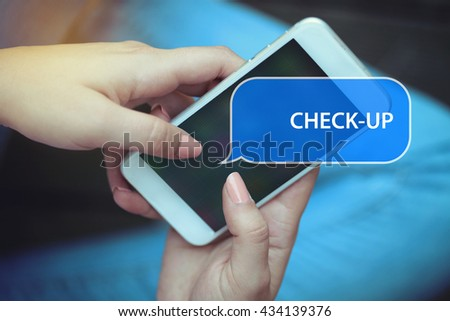 Young women holding mobile phone writen Check-Up on it - stock photo