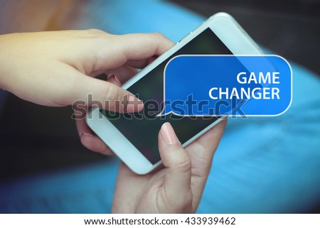 Young women holding mobile phone writen Game Changer on it - stock photo