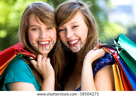 Young women holding shopping bags - stock photo