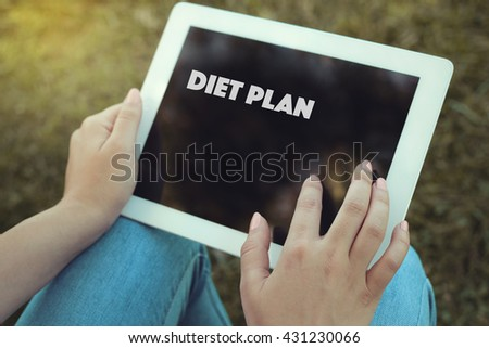 Young women holding tablet writen Diet Plan on it - stock photo