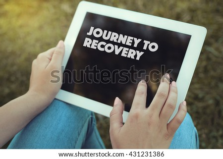 Young women holding tablet writen Journey To Recovery on it - stock photo