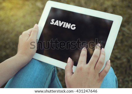 Young women holding tablet writen Saving on it - stock photo