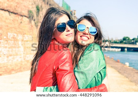 Young women hugging at pier before leaving - Cheerful trendy girls embracing outdoor - Love and friendship concept - Soft vintage filter look with warm tones  focus on left female - stock photo