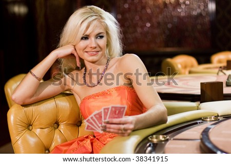 Young women in casino with playing cards - stock photo