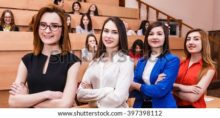 Young women in classroom with students - stock photo