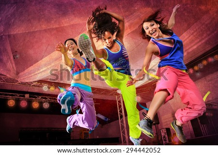 young women in sport dress jumping at an aerobic exercise - stock photo