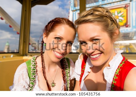 Young women in traditional Bavarian clothes - dirndl or tracht - on a festival or Oktoberfest riding the ferris wheel - stock photo