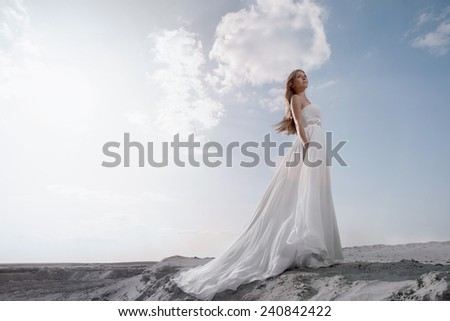 Young women in white wedding floor-length dress with long lower hem waved  in looking up with light blue sky with a lot of clouds behind her - stock photo