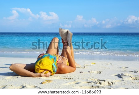 Young women is reading on coral beach, Maldives - stock photo