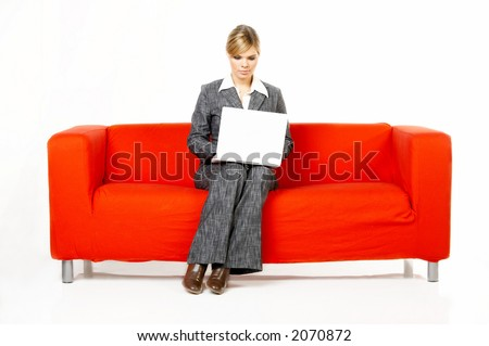 Young women is resting on the couch and surfing the internet on her laptop computer