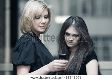 Young women looking at a mobile phone - stock photo