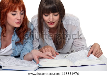 Young women looking up a word in the dictionary - stock photo