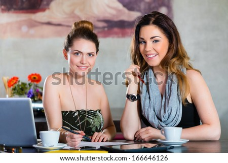 Young women or colleagues working in a cafe or restaurant, on some documents or contract - stock photo