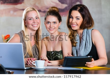 Young women or colleagues working in a cafe or restaurant, on some documents or contract with Laptop and Tablet Computer - stock photo