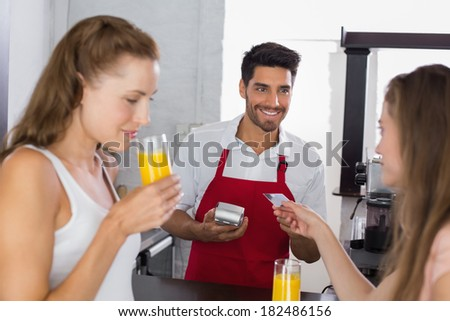 Young women paying bill while drinking orange juice at coffee shop using card bill