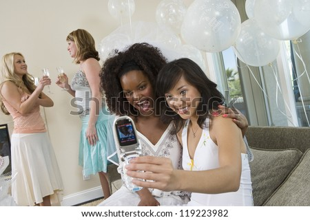 Young women photographing themselves using mobile phone