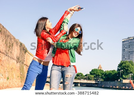 Young women playful girlfriends hands up holding mobile phone at pier - Cheerful female best friends playing as teenagers catching new smartphone each others - Concept of fun and teenage friendship - stock photo