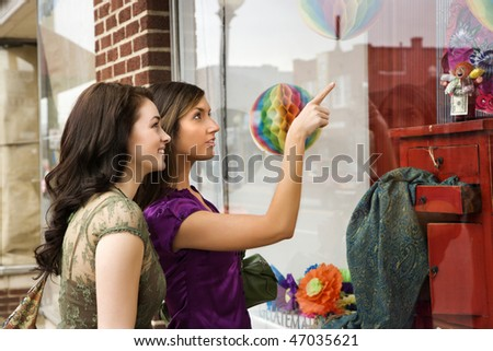 Young women pointing to items in an interior design store window. Horizontal shot. - stock photo