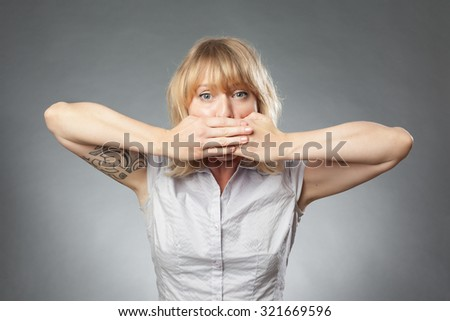 Young women portrait on grey background, covering her mouth - stock photo