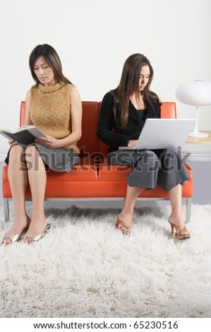 Young women reading on couch