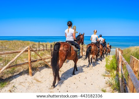 Young women riding horses to sandy beach in Lubiatowo coastal village, Baltic Sea, Poland - stock photo