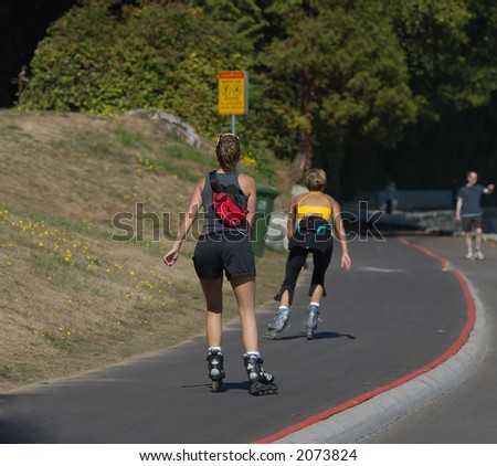 Young women rollerblading on the Stanley park seawall - stock photo