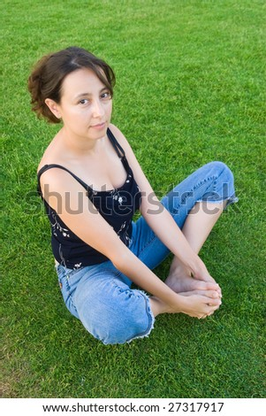 young women sit on the green grass - stock photo