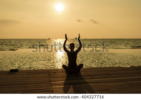 Young women sitting on the beach and enjoy the sunset  - stock photo