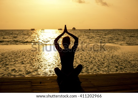 Young women sitting on the beach and enjoy the sunset