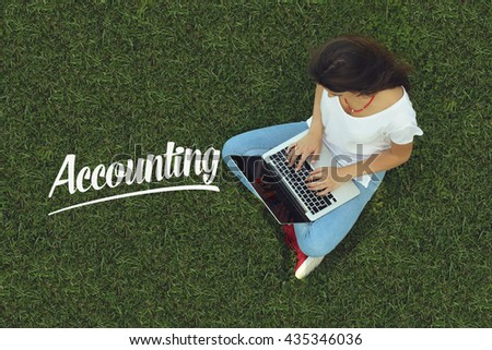 Young women sitting on the grass on a Tablet PC is searching for Accounting. - stock photo