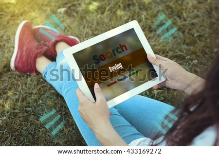 Young women sitting on the grass on a Tablet PC is searching for Saving. - stock photo