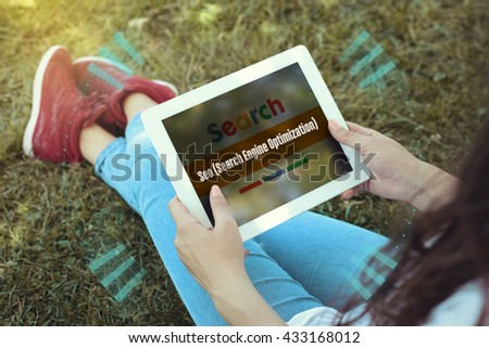 Young women sitting on the grass on a Tablet PC is searching for Seo (Search Engine Optimization). - stock photo