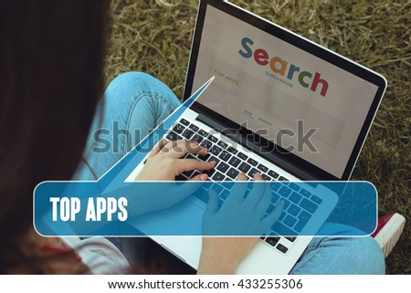Young women sitting on the grass on a Tablet PC is searching for Top Apps.