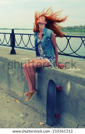 Young women sitting with her skate board on concrete street parapet with her red hair flying in the wind - stock photo