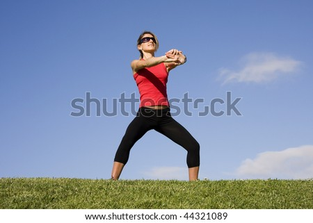 Young women stretching her arms isolated on a blue sky - stock photo