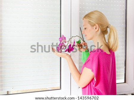 Young women take care of the flower of orchid. - stock photo