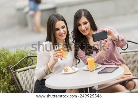 Young women taking photo with cellphone in the cafe - stock photo