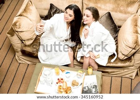 Young women taking selfie in bathrobes - stock photo