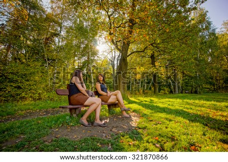 Young women talk with herself in summer park. One woman both roles
