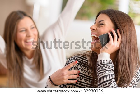 Young Women Talking On Cell Phone And Laughing, Indoors