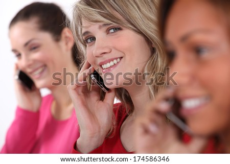 Young women talking on their mobile phones - stock photo