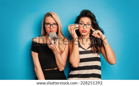 Young women talking with tin can telephone against blue background. Conceptual funny image for communication. - stock photo