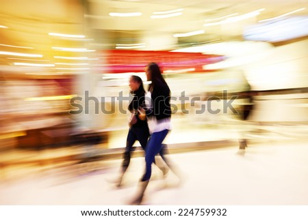 Young women walking past shop front window - stock photo