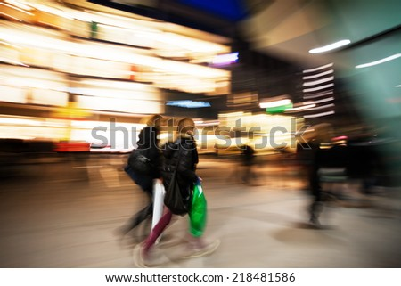Young women walking past window display in clothes shop at dusk - stock photo