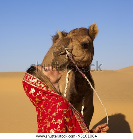 Young women wearing a saree and kissing a camel on the dunes of the Thar Desert, Rajasthan - India - stock photo