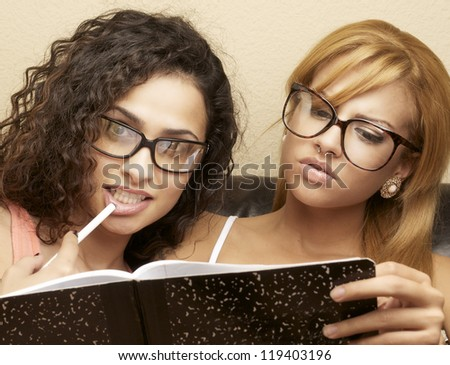 Young women wearing glasses taking notes studying for college. - stock photo
