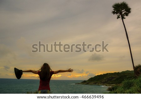 young women winning success   with raised hands standing on top of a mountain. happy and sucsess,phuket Thailand