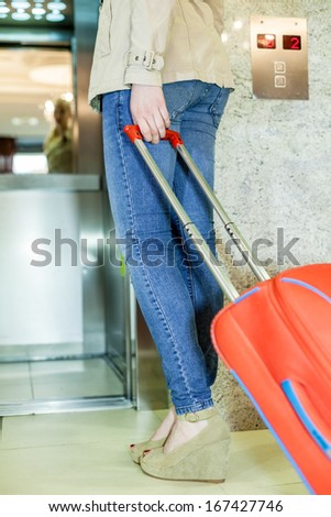 Young women with a suitcase in the front of lift, soft focus - stock photo