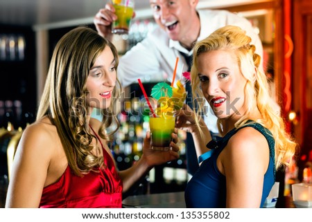 Young women with cocktails in bar or club, the bartender is mixing drinks